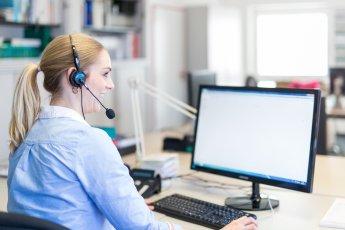 Mitarbeiterin mit Headset am Computerbildschirm