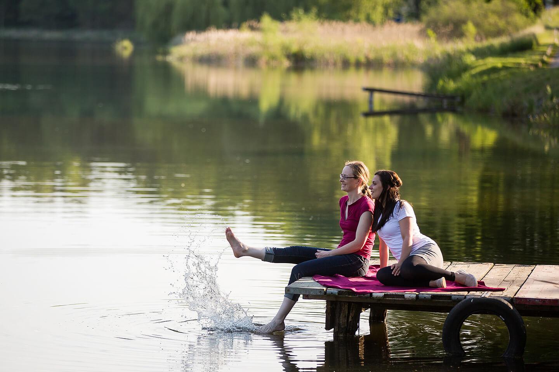 Stimmungsfoto von zwei jungen Damen auf einem Steg am See