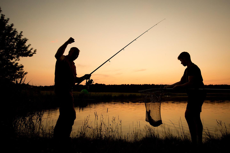 Angelfoto zwei erfolgreicher Angler im Sonnenuntergang