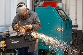 Handwerker mit Funkenflug an der Schleifmaschine