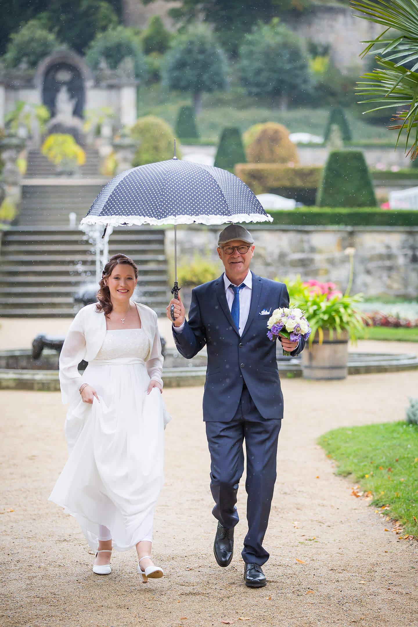 Vater führt die Braut im Schlosspark zur Trauungszeremonie