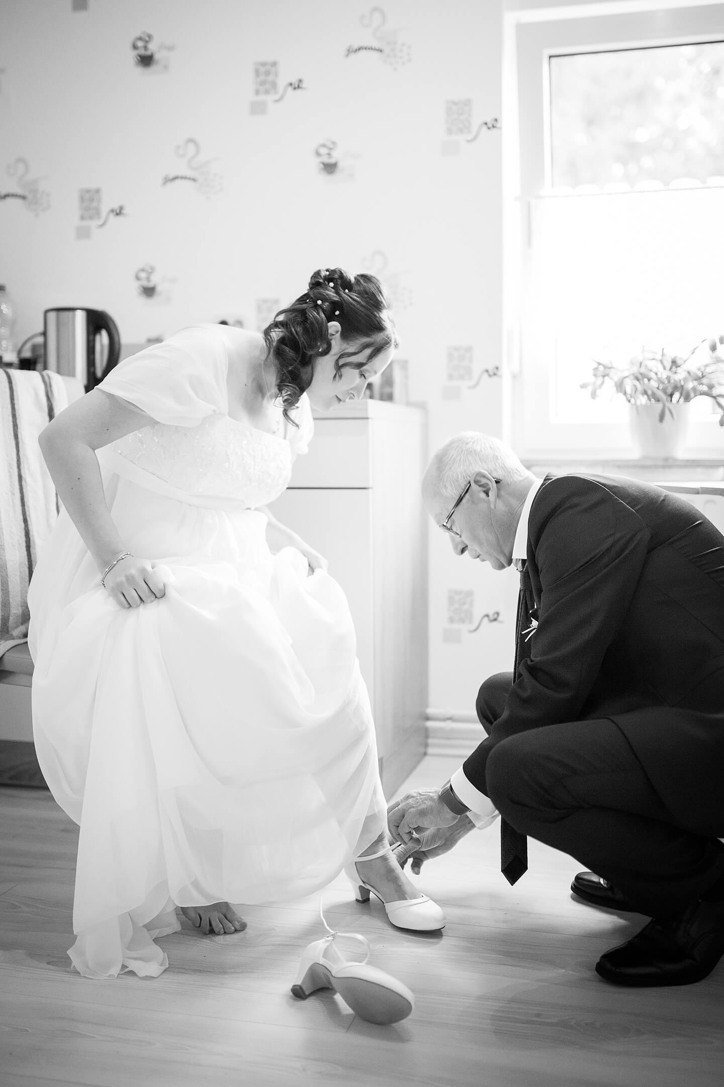 Vater zieht seiner Tochter die Brautschuhe an