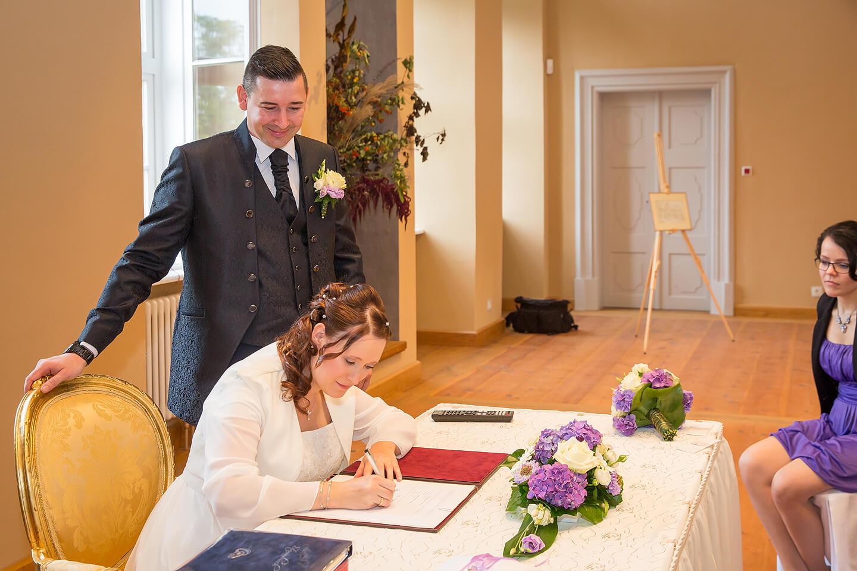Braut leistet Unterschrift im Standesamt