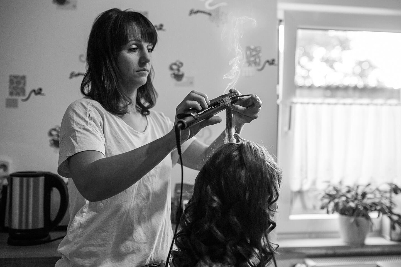 Braut bei den morgendlichen Vorbereitungen mit der Friseurin