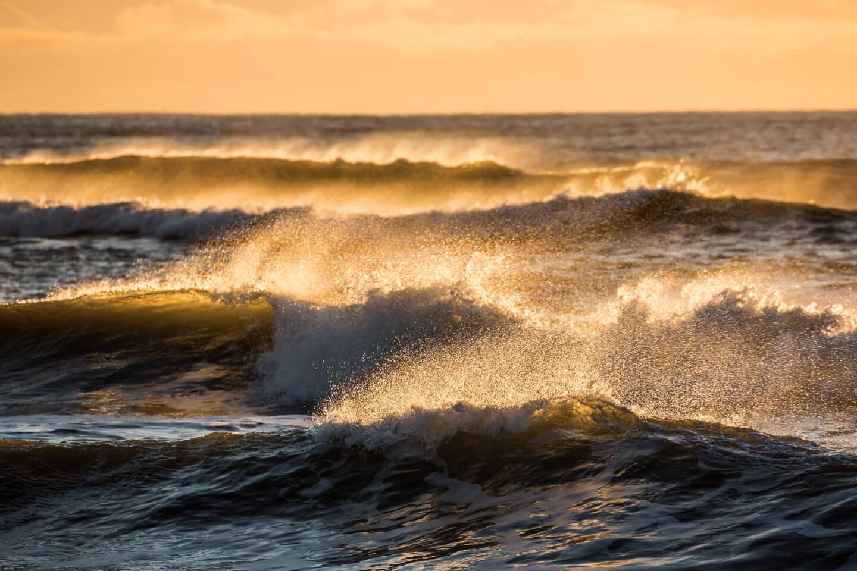 Wellenformationen am schwarzen Strand von Island