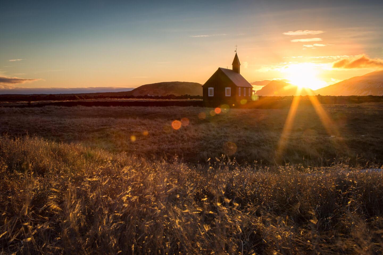 Die schwarze Kirche bei Budir in der untergehenden Sonne mit reichlich Lens flares im Bild