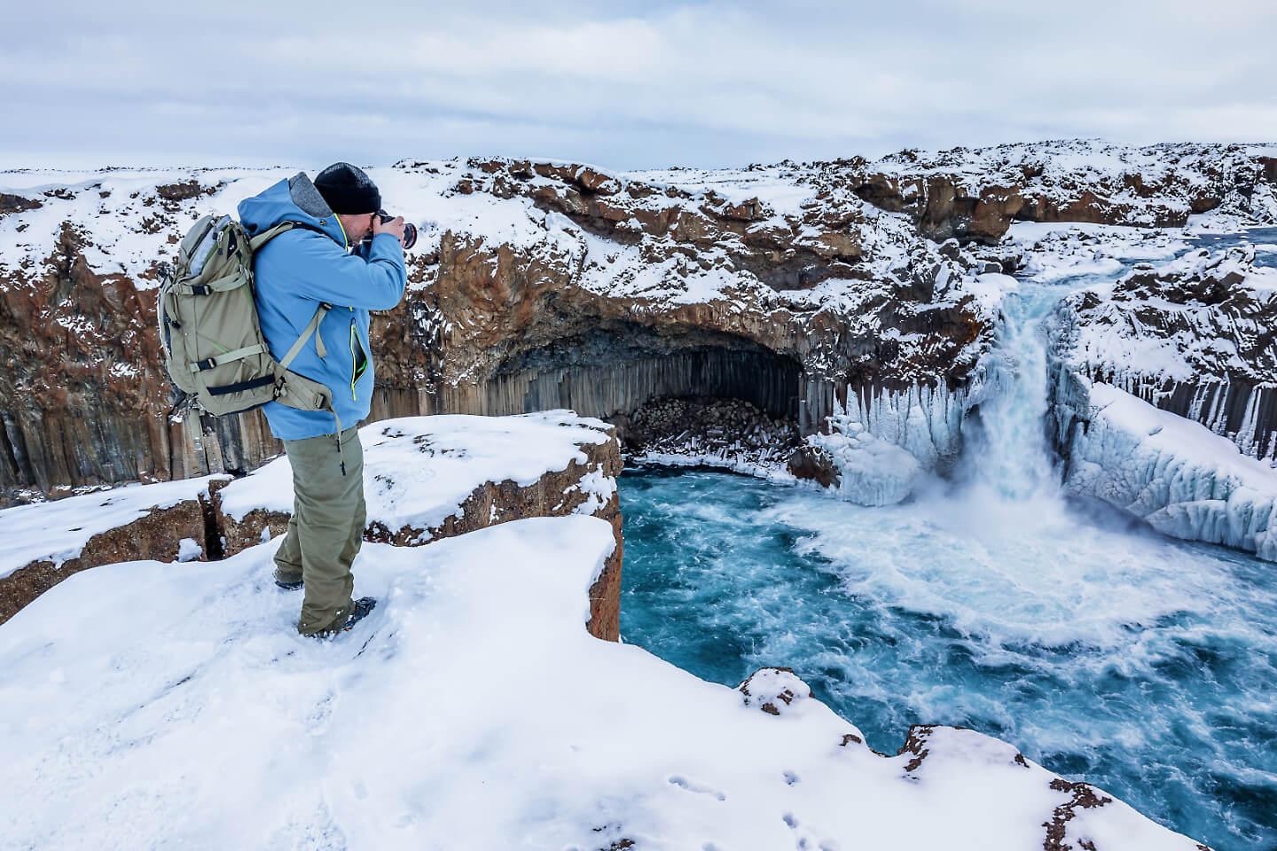 Fotograf Florian Läufer bei einer freien Arbeit im winterlichen Island an dem Wasserfall Aldeyarfoss