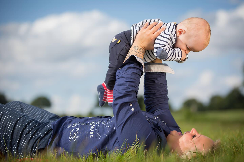Outdoorshooting mit einem Baby und seiner stolzen Mama auf einer grünen Sommerwiese