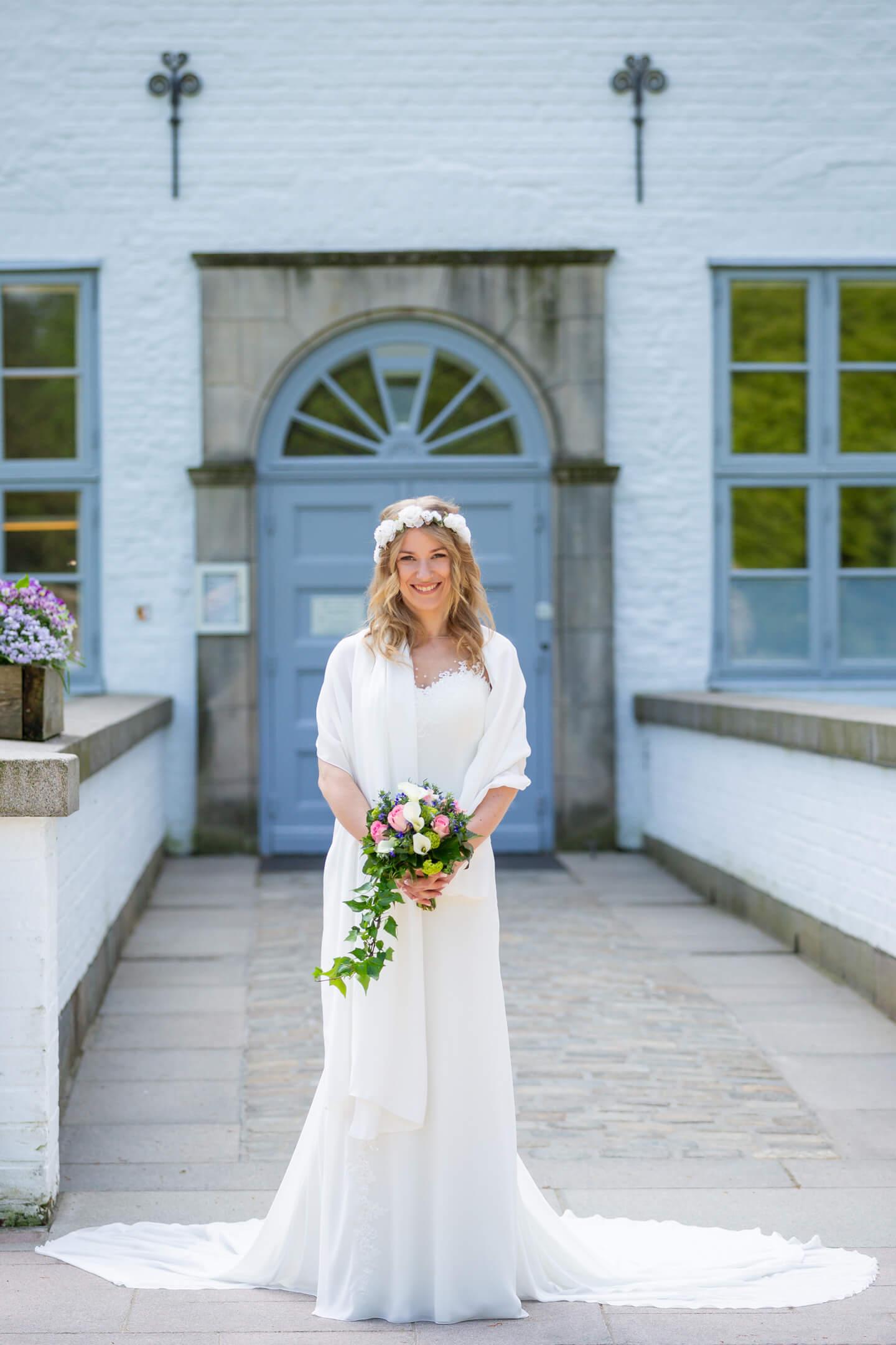 Braut wartet auf den Bräutigam vor der standesamtlichen Hochzeit im Schloss Ahrensburg