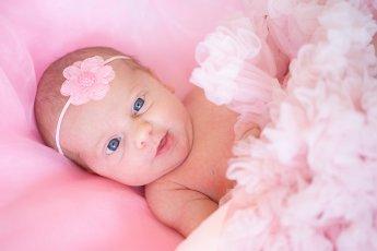 Neugeborenes Mädchen in rosa Studioumgebung mit strahlend blauen Augen