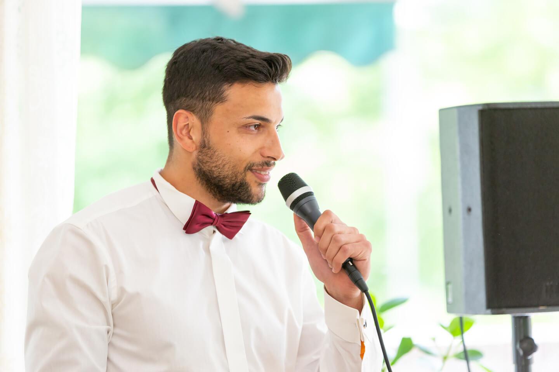 Trauzeuge hält eine Rede mit Mikrofon