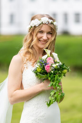 Braut mit Blumenkranz und Brautstrauss vor dem Ahrensbuger Schloss