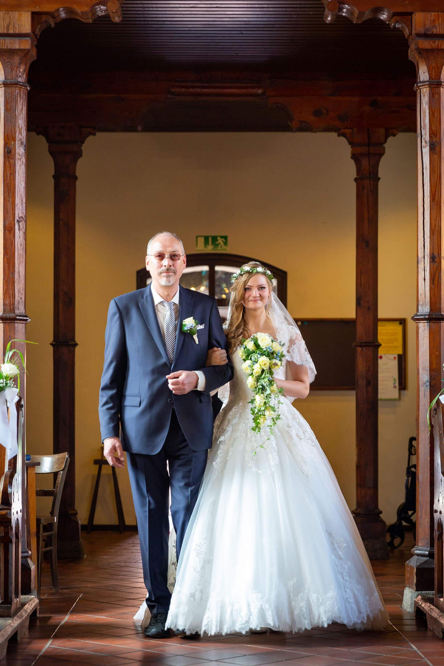 Brautvater geleitet seine Tochter zum Altar