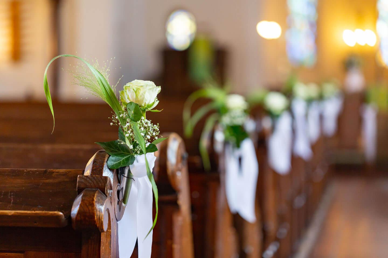 Blumengestecke als Schmuck an den Holzbänken in der Kirche