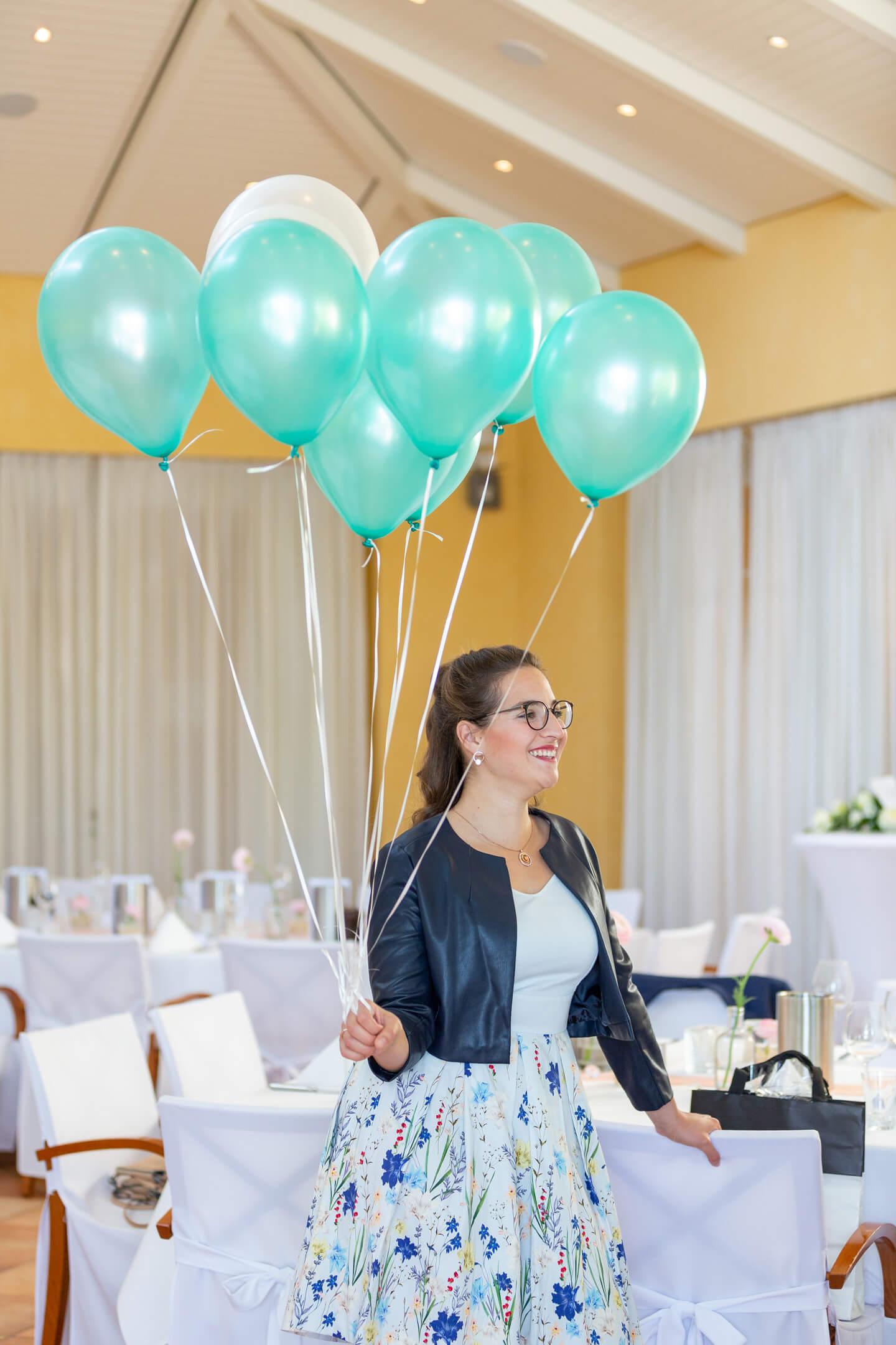 Junge Frau hält Luftballons für Hochzeitsfeier