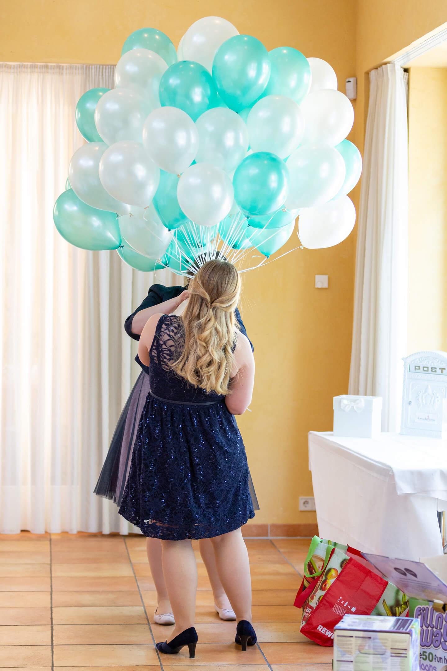 Helfende Hände, die ich während einer Hochzeitsreportage beim Vorbereiten von Ballons fotografiert habe