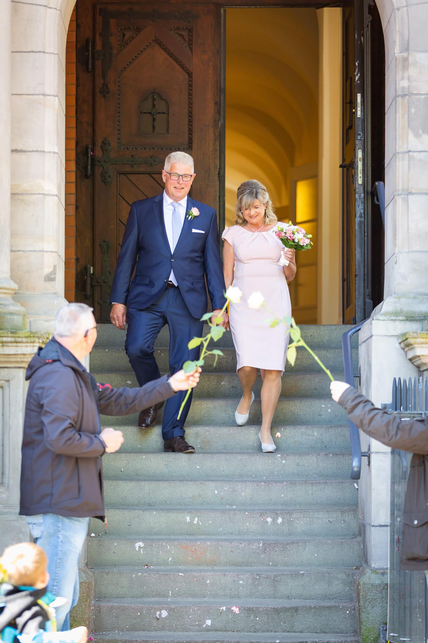 Hochzeitspaar schreitet aus dem Standesamt die Stufen herunter