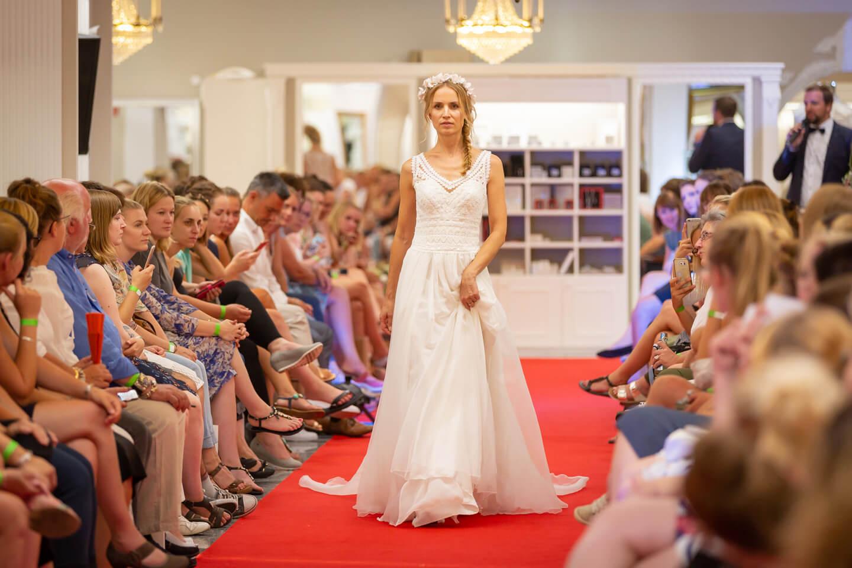 Model präsentiert unter den Blicken der Gaeste ein Hochzeitskleid auf dem Catwalk