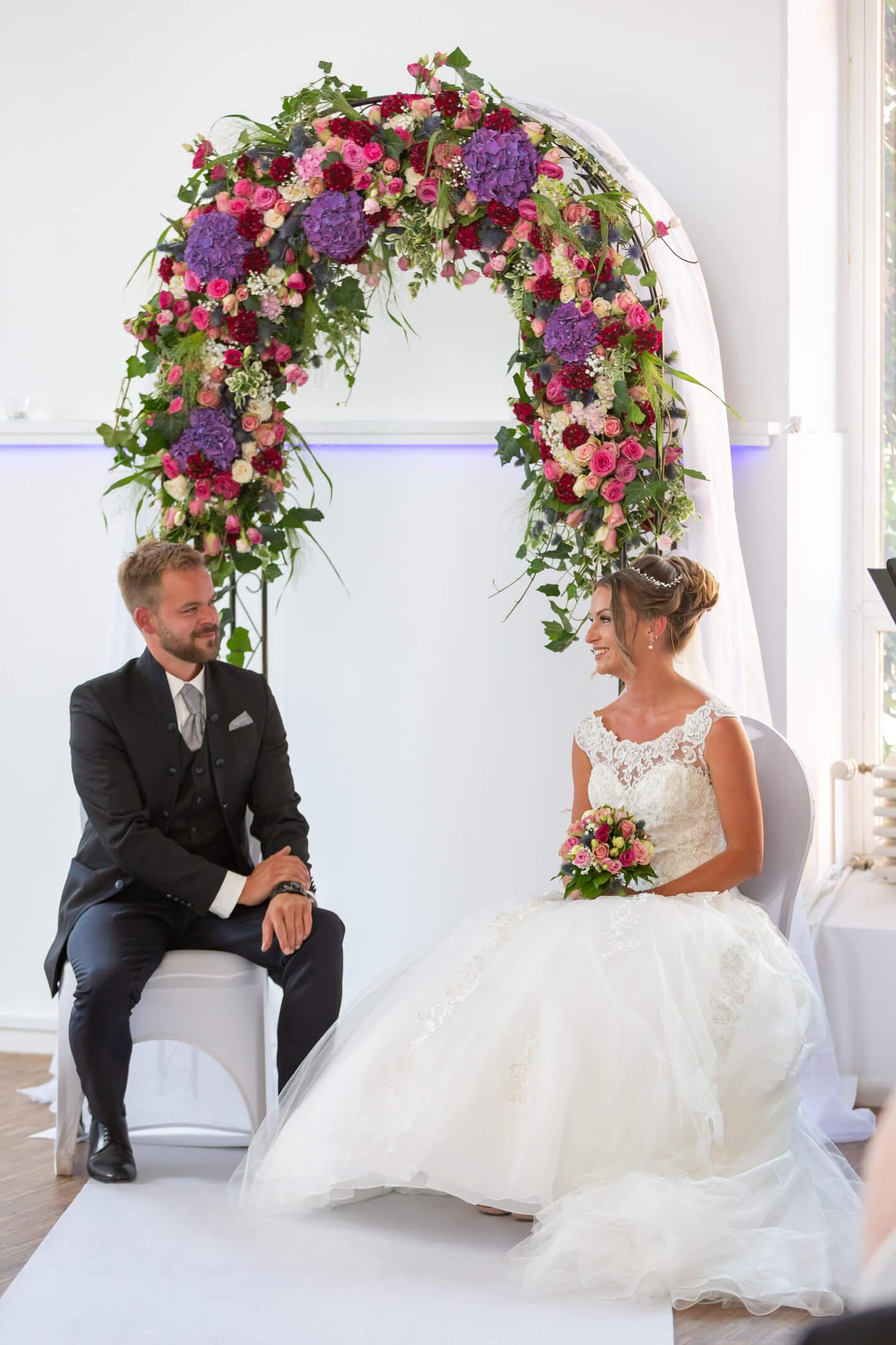 Hochzeitspaar mit Blumenbogen bei ihrer Hochzeit in der alten Friesenbrauerei
