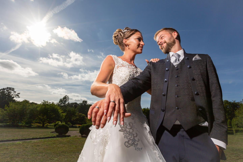 Brautpaar zeigt die Eheringe im Gegenlicht