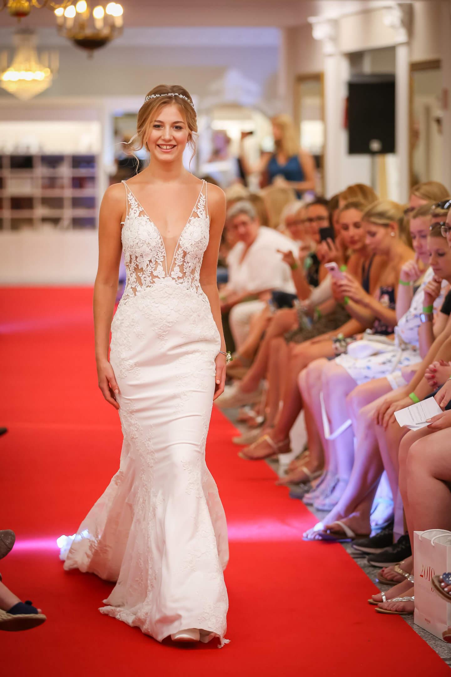 Eng geschnittenes Hochzeitskleid auf dem Catwalk bei Laue Festgarderobe präsentiert