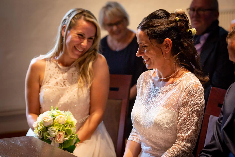 Trauzeugin lacht Braut im Standesamt an