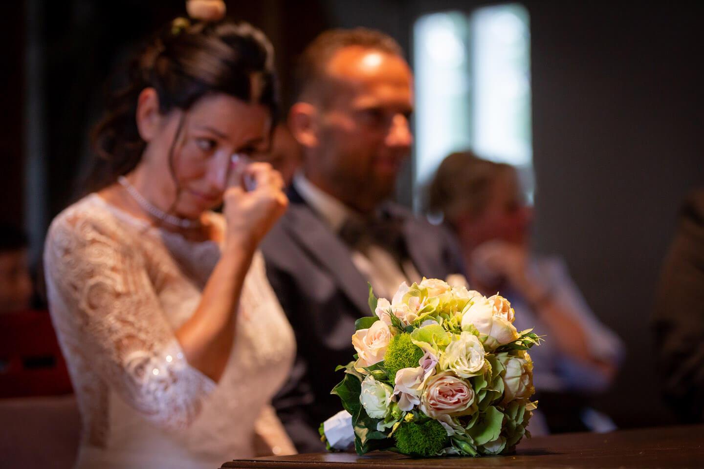 Brautstrauss - im Hintergrund ist verschwommen das Brautpaar zu erkennen