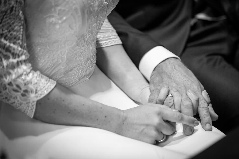 Brautpaar hält sich die Haende während der Hochzeit in der Trittauer Mühle