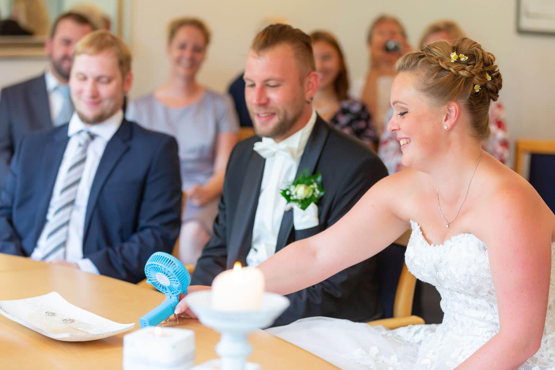 Braut schiebt den kuehlenden Ventilator zum Gatten hinueber