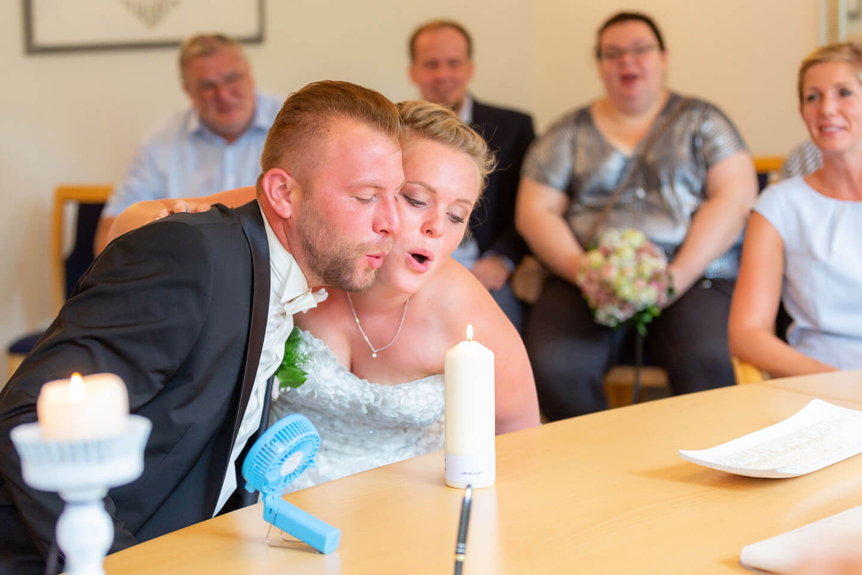 Hochzeitspaar pustet gemeinsam eine Kerze aus
