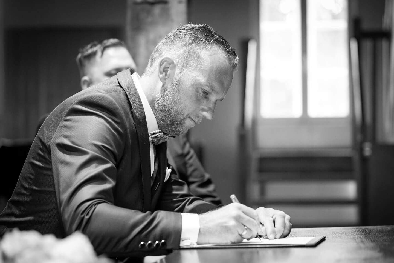Braeutigam unterschreibt die Heiratsurkunde in der Trittauer Wassermuehle