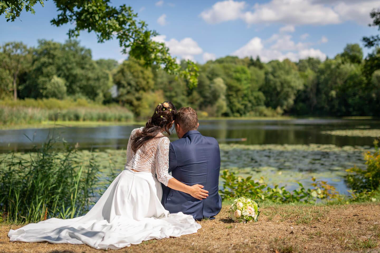 Hochzeitspaar blickt vertraeumt auf den Trittauer Muehlenteich