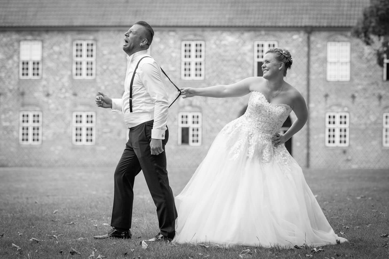 Witziges Hochzeitsfoto - Braut hält Mann am Hosenträger fest
