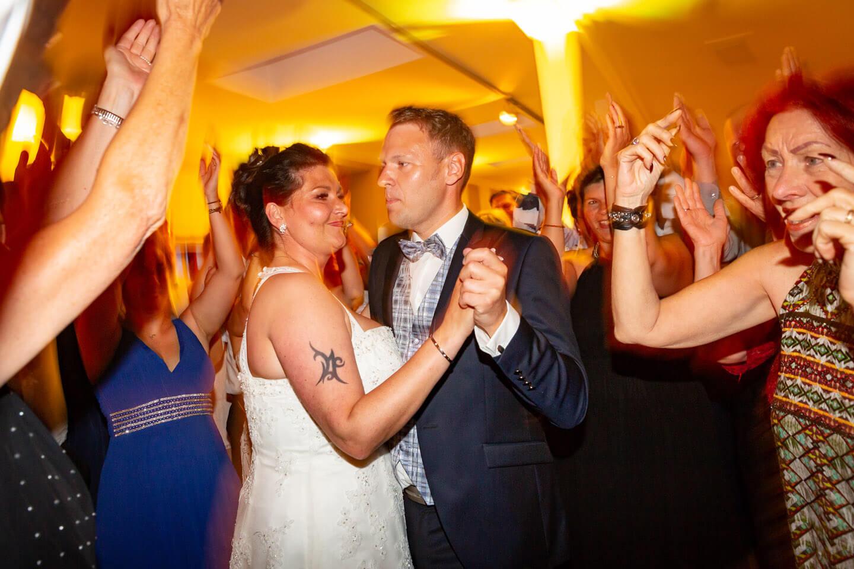 Hochzeitspaar eng von Gästen umringt auf der Tanzfläche.