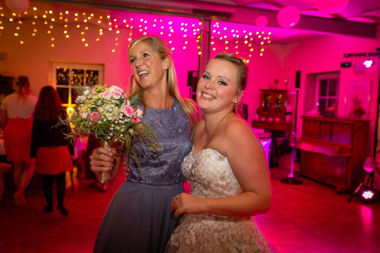 Braut mit Faengerin vom Brautstrauss