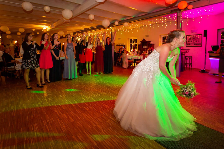 Brautstrauss werfen während der Hochzeitsfeier
