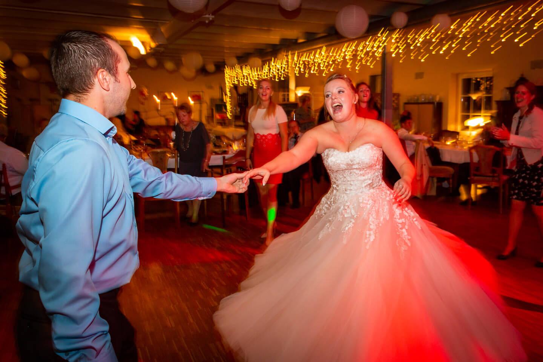 Ausgelassene Stimmung bei dieser Hochzeitsreportage. Braut tanzt mit Hochzeitsgast.