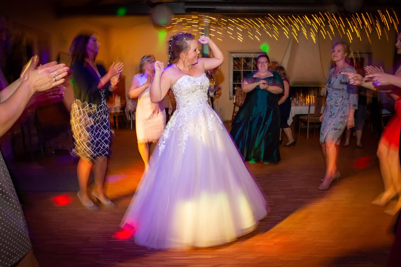 Braut tanzt umringt von ihren Freundinnen.