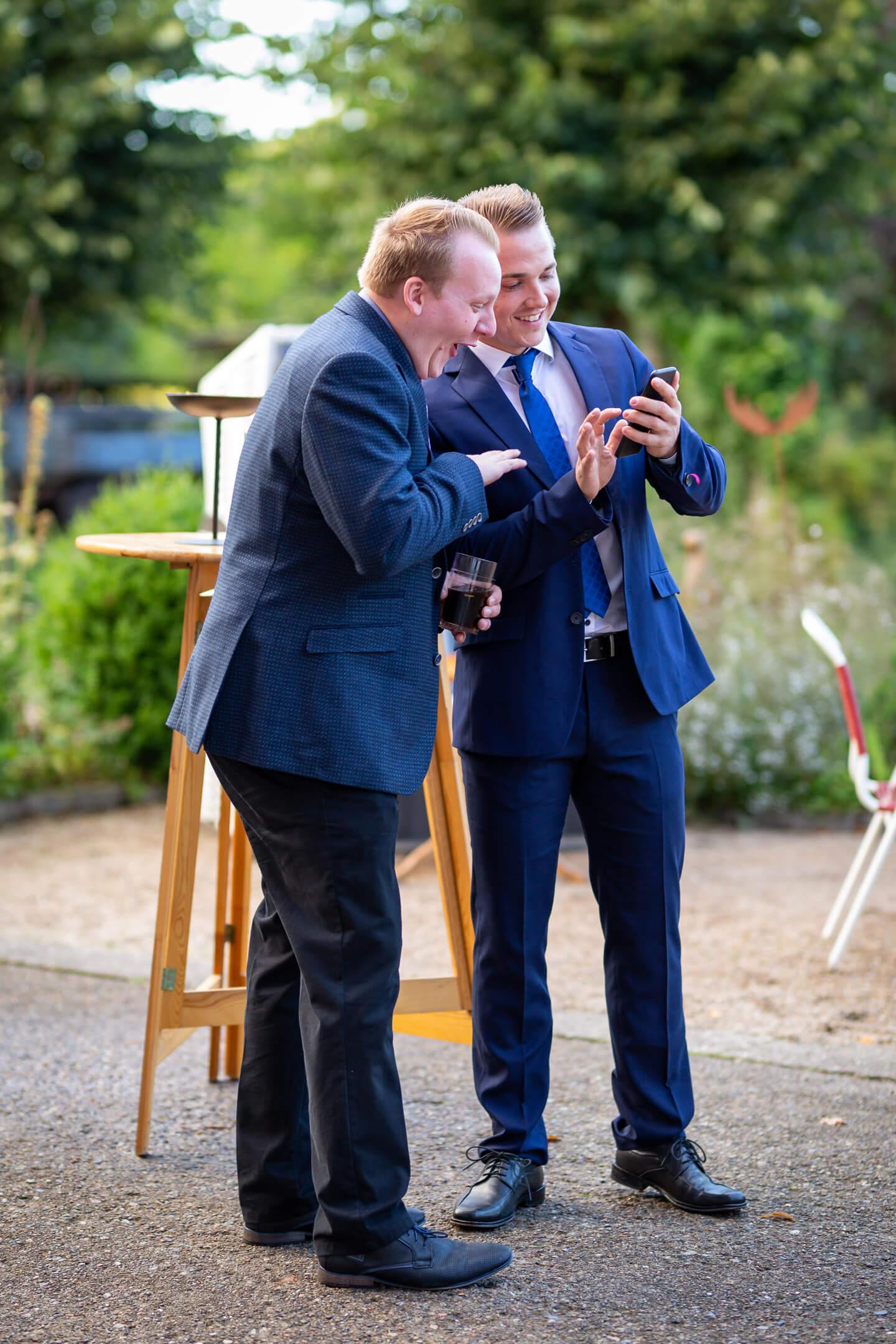 Zwei Gäste schauen lachend auf ein Handy während einer rauchpause vor der Tür der Hochzeitslocation