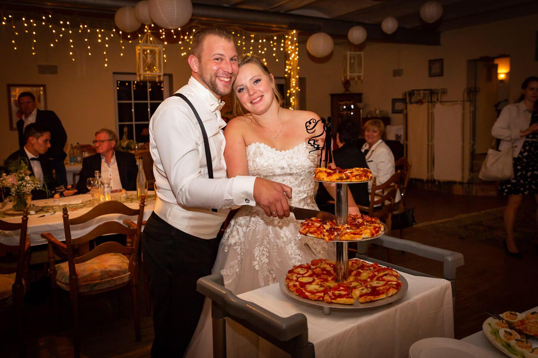 Hochzeitspaar schneidet Hochzeitspizza um Mitternacht an.