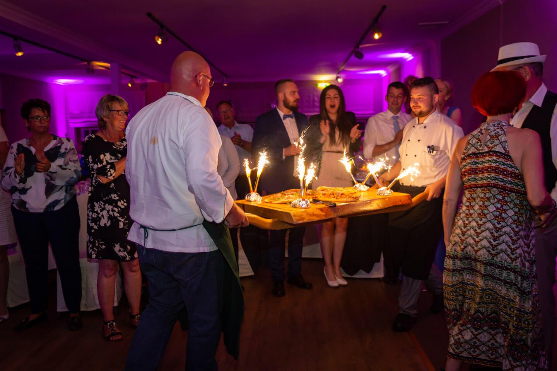 Hochzeitspizza statt Hochzeitstorte. Und die wird hier mit einem kleinen feuerwerk von zwei Köchen in den Festsaal getragen.