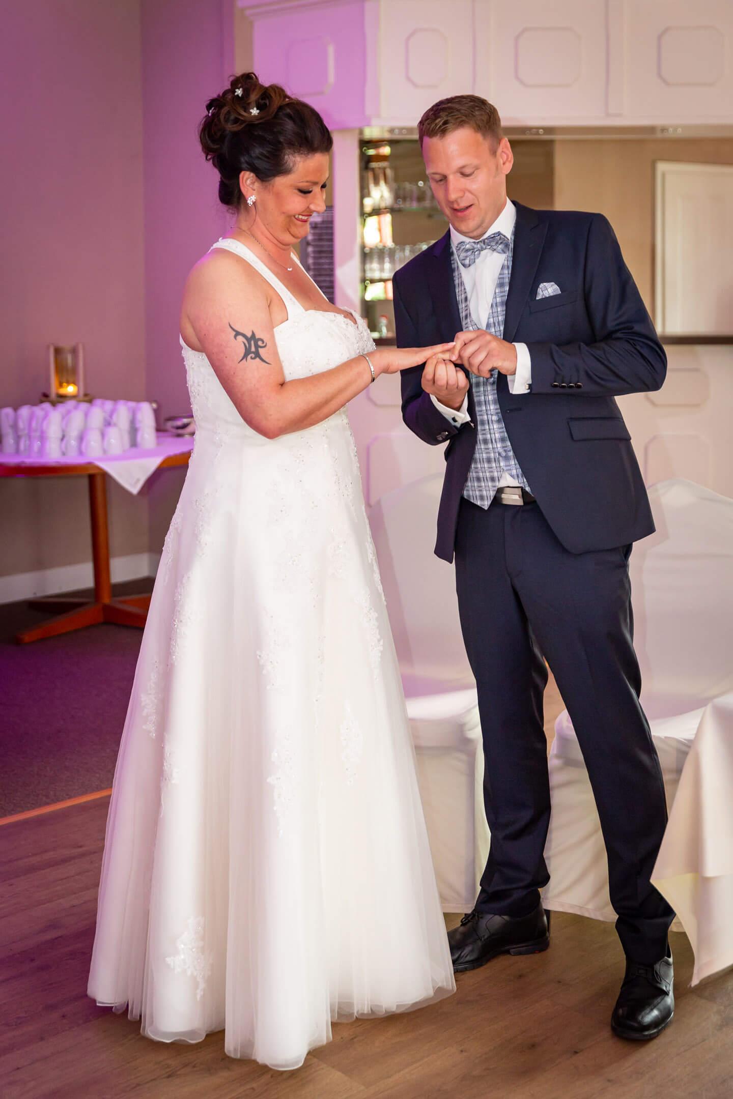 Bräutigam steckt seiner Frau bei freier Trauung den Ehering auf.