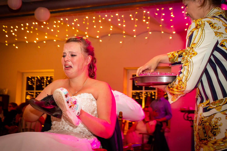 genau im richtigen Moment auf den Auslöser gedrückt: Braut verzieht das Gesicht, nachdem sie beim Schuhspiel einen Kurzen getrunken hat.