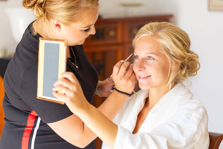 Braut blickt in den Spiegel während sie geschminkt wird.