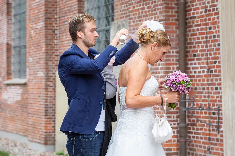 Braut wird an der Kirche vom Friseur gestylt