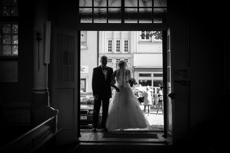 Braut mit Brautvater im Eingangsbereich der Kirche im Gegenlicht