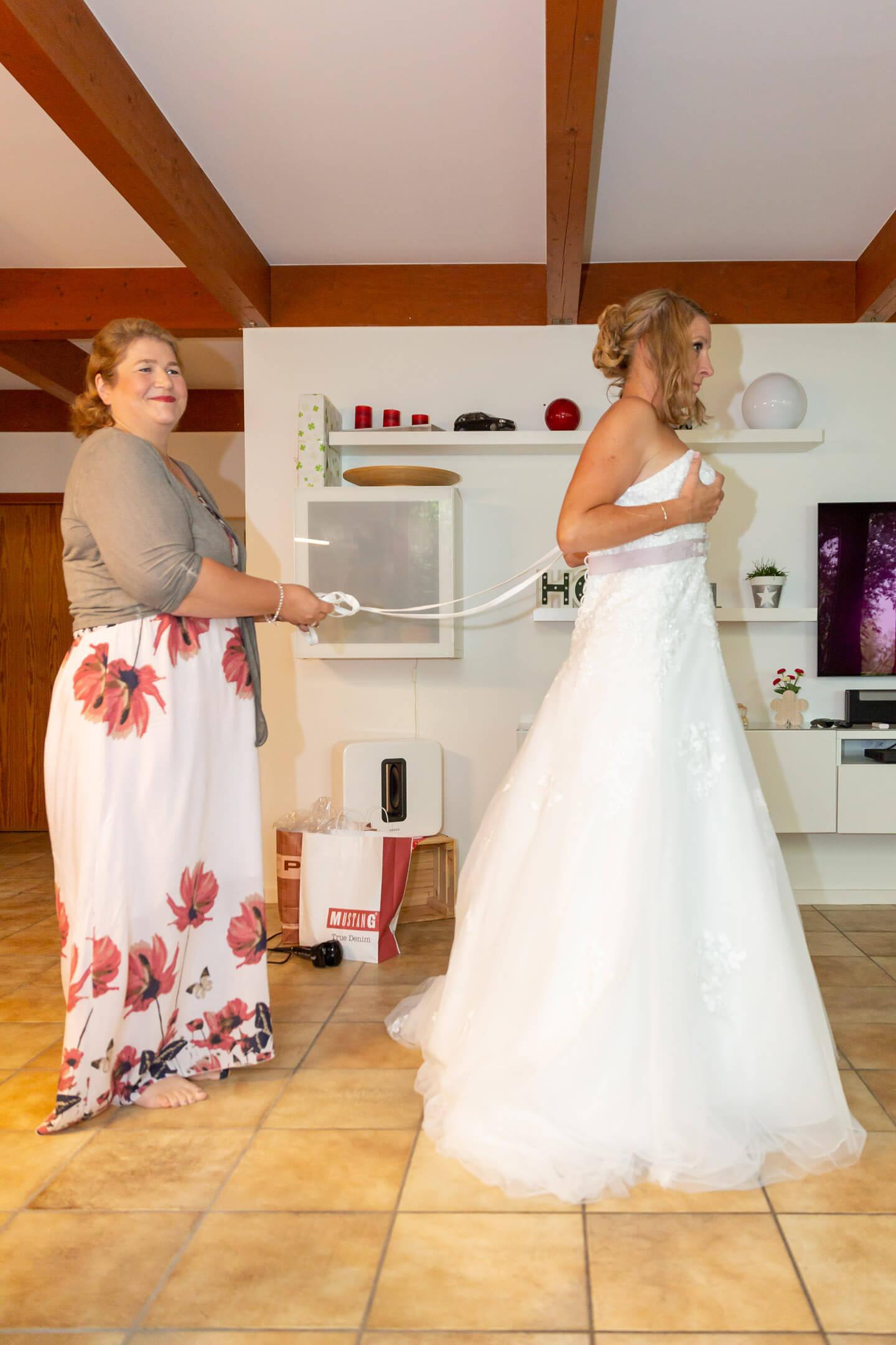 Braut wird in ihrem Hochzeitskleid eingeschnuert