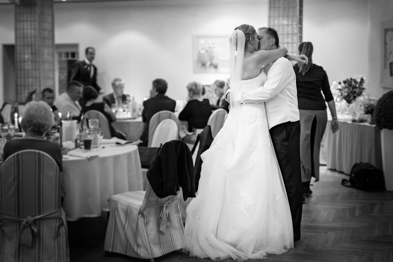 Hochzeitspaar kuesst sich auf ihrer Hochzeitsfeier