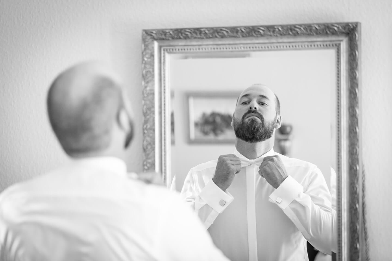 Bräutigam zupft sich die Fliege vor dem Spiegel zurecht