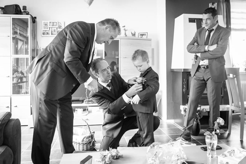 Dem Kind des Brautpaares werden die Blumen an den Anzug gesteckt